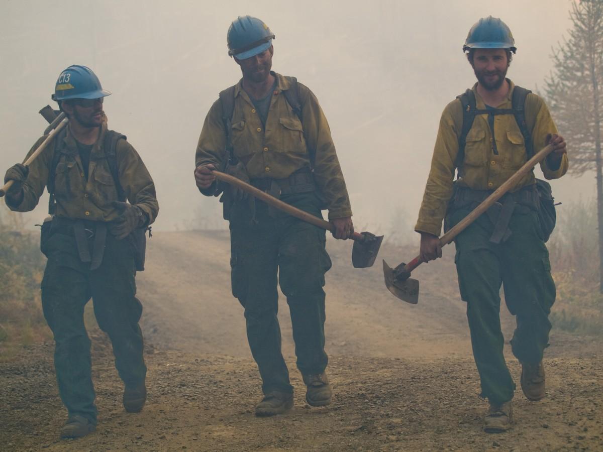 3 fire fighters walking on dirt road